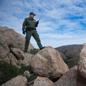 Border patrol agent Barona checks out the area after receiving a call of seismic activity on a trail in Tecate, California