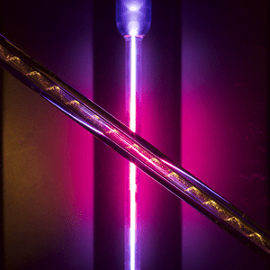 Overall 2nd DNA of an optical fibre by Rob Francis-Jones, University of Bath: The soft magenta glow of a hydrogen lamp highlights the fundamental building block of an optical fibre, a hollow glass preform that can be drawn down to create a fibre the width of a human hair. Unlike optical fibres used in connecting homes to the internet, this fibre can be used to trap a gas within its hollow core. The helical defect encircling the core was the result of a stress caused in the glass during the fabrication process.