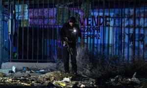 A police officer investigates a crime scene in eastern Tijuana, Mexico.