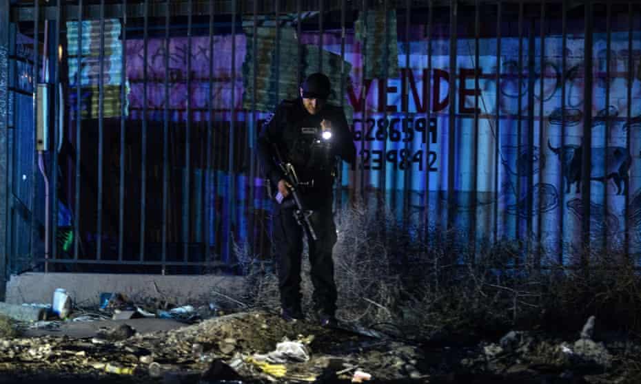 A police officer investigates a crime scene in eastern Tijuana, Mexico.