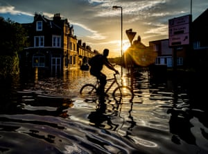A cyclist ridess through flood water in Carlisle, Cumbria after severe flooding across the county