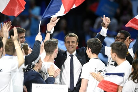 Macron raises his hands on stage surrounded by his supporters as after delivering a speech during a campaign rally at the Bercy Arena in Paris on Monday.