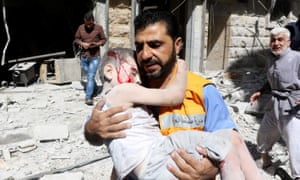 A search and rescue worker rescues a child from the debris of buildings after the barrel bomb attack staged by Syrian army in Aleppo, Syria on 25 July, 2016.