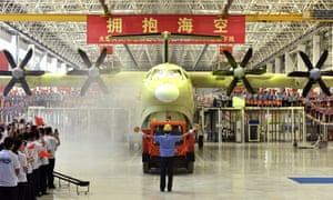 Chinese workers wave national flags as the Amphibious aircraft AG600 is rolled off a production line in Zhuhai in south China's Guangdong Province.