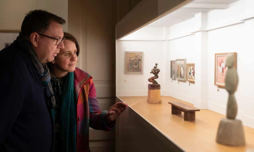 Two people looking into a glass display cabinet to see what appears to be a scale model of an art gallery, with tiny paintings on white walls, and a wooden floor and benches
