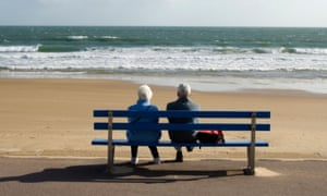 Pensioners sitting on bench at the seaside