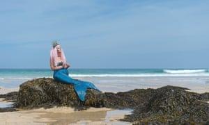 Laura Evans in mermaid tail on a rock