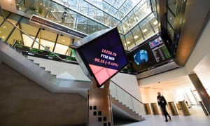 A woman walks through the central atrium at the Londson Stock Exchange in central London