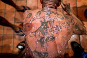 Portobelo, Panama: Edwin Villarreta has candle wax dripped on to his back during a penitence walk to the church of Saint Philippe