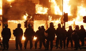 Riot police stand in line as fire rages through a building in north London after Mark Duggan was shot dead by police.