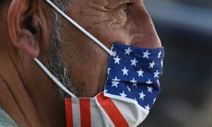 A man wears an American flag face mask on a street in Hollywood, California, after the indoor mask mandate returned to Los Angeles. With the Delta variant pushing US Covid cases back up, fully vaccinated people are wondering whether they need to start masking indoors again. Covid vaccines remain extremely effective against hospitalization and death.