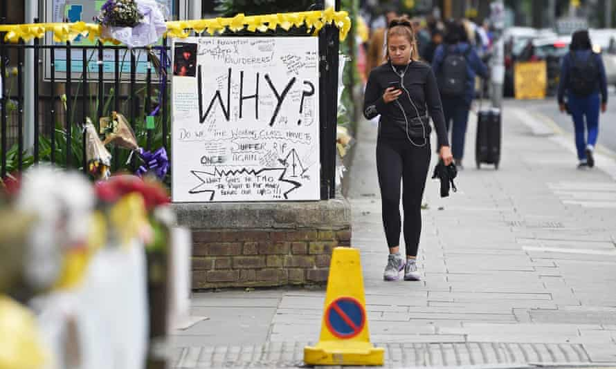 A woman walks past flowers and messages of condolences near Grenfell Tower.
