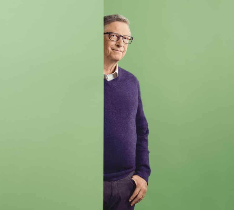 Bill Gates wearing a purple jumper and peering out from behind a green wall