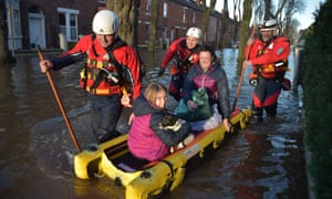 A rescue team helps evacuate people from their homes in Carlisle after Storm Desmond.