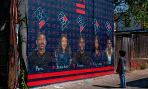 Lauryn Renford, 17, looks at a mural by Martin Swift depicting teenage gun violence victims in Washington DC.