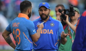 India's Rohit Sharma is interviewed by his captain Virat Kohli on the pitch after India's victory.