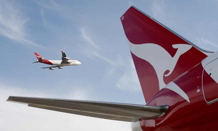 A Qantas 767 passenger jet flies over Sydney Airport in Sydney, Australia, while another plane sits on the tarmac