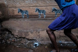 Three zebras are painted on a wall by Portuguese street artist Ricardo Romero as part of his Project Matilha to raise awareness of human and animal rights in the Kibera slum of Nairobi