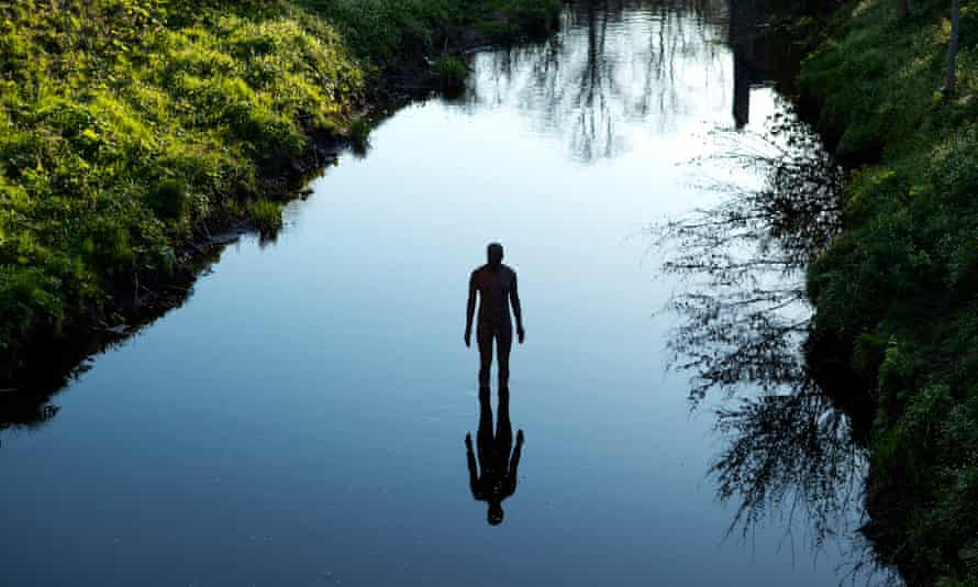 One of artist Antony Gormley's 6 Times statues in the Water of Leith.