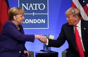 Donald Trump shakes hands with Angela Merkel