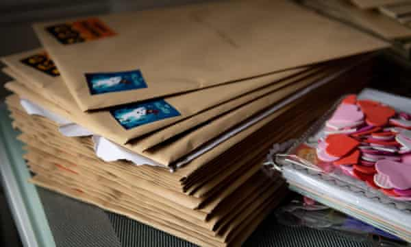 a pile of letters in envelopes next to a collection of paper hearts.
