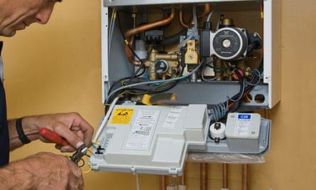 A heating engineer repairing a gas boiler.