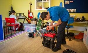 Elias, 14, works on an engine