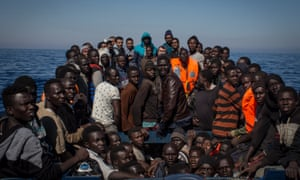 migrants wait to be rescued from a small wooden boat