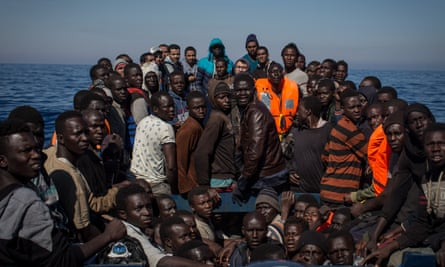 Refugees and migrants wait to be rescued from a boat in the Mediterranean