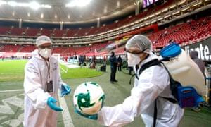 Pracownicy służby zdrowia dezynfekują piłki przed meczem piłki nożnej między Guadalajarą a Ameryką w stanie Jalisco w Meksyku.