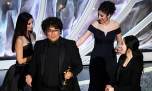 Bong Joon-ho, director of Parasite, accepts one of his Oscars from Penélope Cruz, left