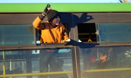 A boy waves from an evacuation bus in Aleppo.