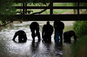 Police officers search a river in Queen Elizabeth Gardens in Salisbury, 19 July