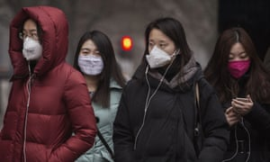 Chinese women wear masks as they wait to cross the street