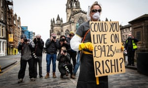 A young woman wearing a mask and gloves holds up a sign saying 'Could you live on £94.25/week Rishi?'