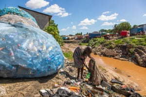 Ramadhan Mohamed, a waste picker, collects plastic bottles along the riverbank.
