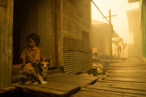 Child and cat seen at Sei Ahass village, where the air is engulfed with thick haze from the forest fires