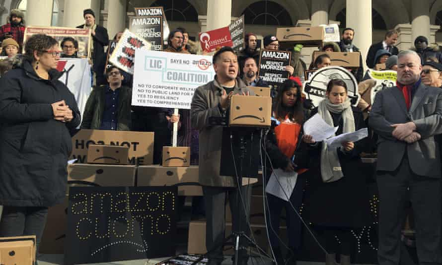 New York assemblyman Ron Kim, center, speaks at a rally opposing New York's deal with Amazon on the steps of city hall on 12 December.