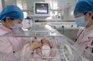 Handan, China: Nurses take care of newborns in an incubator in a hospital in north China's Hebei province