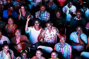 People watch the outdoor premiere of a Haitian film