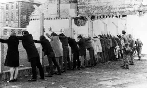 A scene from Derry in 1971 showing people being lined up against a wire fence by british soldiers