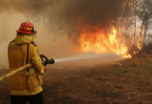 Firefighters work to contain a bushfire along Old Bar Road in Old Bar, New South Wales on Saturday.