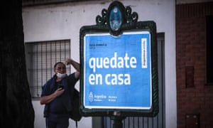 A man waits in front of a poster with a message from the government to ask people to comply with quarantine rules, in Buenos Aires, Argentina.
