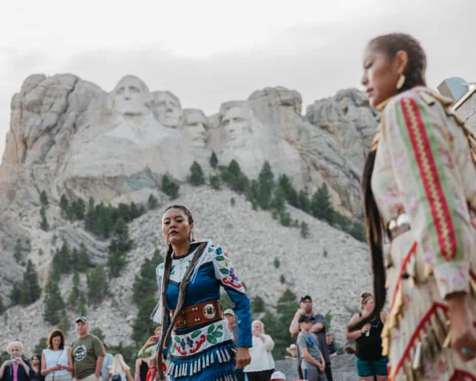 Sunni Begay (dark blue) and Dion Tapahe (yellow) of the Jingle Dress Project dance at Mount Rushmore. They were invited by Red Dawn Foster, a state senator representing the Pine Ridge area.