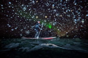 Myrtille Heissat from France rides a stand-up paddle under the Northern Lights in the Lofoten islands, within the Arctic Circle.