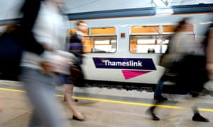 Commuters walk past Thameslink train