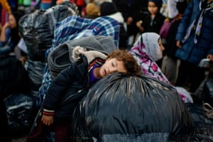 A child rests on bags as migrants and refugees wait to depart from Lesbos to Athens