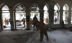 Afghan municipality workers sweep Baqir-ul Ulom mosque after the suicide bomb attack