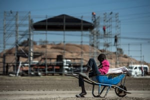 A child plays on a wheelbarrow near a stage where commemorations for the fourth anniversary of the Marikana massacre will be held