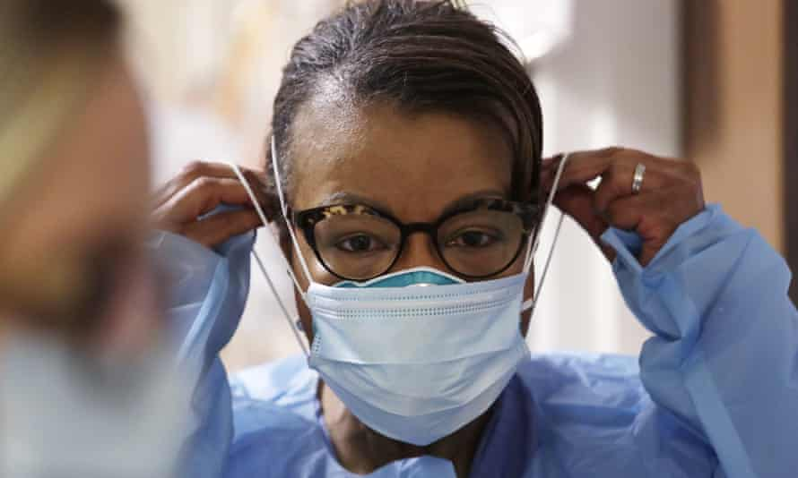 A respiratory therapist pulls on a second mask over her N95 mask before adding a face shield as she prepares to treat a Covid-19 patient in Seattle in May 2020, a time when many healthcare workers lacked personal protective equipment.